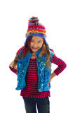 Girl in Colorful Winter Hat and Vest. A young girl with long brown hair and a smile on her face stands with hands on her hips, wearing a whimsical winter hat royalty free stock photos