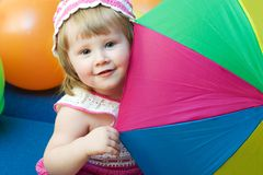Girl with colorfull umbrella. Portrait of cute little girl with colorful umbrella and balloons Stock Images