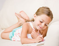 Girl coloring in coloring book. Girl drawing in a coloring book Royalty Free Stock Photo