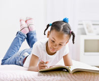 Girl coloring in coloring book Stock Photography