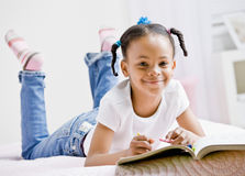 Girl coloring in coloring book. Happy girl coloring in coloring book Royalty Free Stock Images