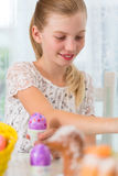 Girl is coloring Easter eggs by painting on them Stock Image