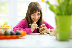 Girl coloring Easter eggs Stock Photography