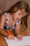 Girl coloring on floor. Girl laying on floor drawing Royalty Free Stock Image
