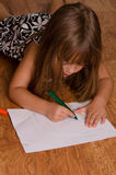Girl coloring on floor. Girl coloring on the kitchen floor Royalty Free Stock Images