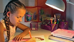 Girl coloring her drawing at the desk in the evening stock video footage