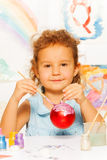 Girl coloring New Year ball for Christmas tree Royalty Free Stock Photography