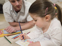 Girl Coloring Pictures With Father Looking At It Royalty Free Stock Photos