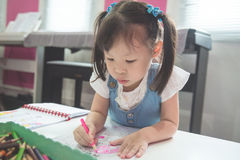 Girl coloring with wooden pencils at the school Stock Images