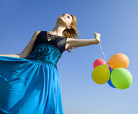 Girl with colour balloons at blue sky background. Royalty Free Stock Photography