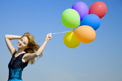Girl with colour balloons at blue sky background. Royalty Free Stock Photo
