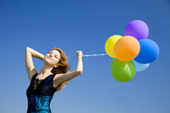 Girl with colour balloons at blue sky background. Royalty Free Stock Image