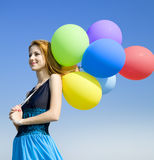 Girl with colour balloons at blue sky background. Stock Images