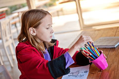 Girl with colouring page, choosing Royalty Free Stock Image