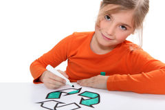 Girl colouring recycling sign. Girl colouring in recycling sign Stock Image