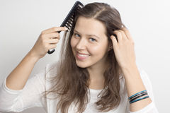 A girl with a comb and a bracelet Stock Images