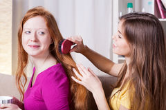 Girl combing hairs her friend Royalty Free Stock Photography