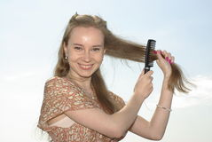 Girl combing her hair Stock Image