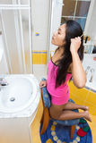 Girl combing her hair Royalty Free Stock Photography