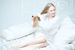 Girl combing her hair in bed Royalty Free Stock Images