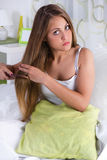 Girl combing her hair in bed Royalty Free Stock Photos