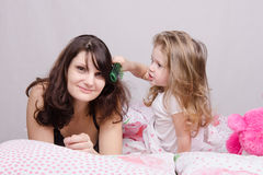Girl combing her hair with enthusiasm mum Stock Photography