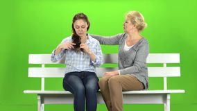 Girl is combing her hair. Green screen. Girl is combing her hair, she and her mother are sitting on a white wooden bench. Green screen stock footage