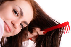 Girl combing her hair red comb Royalty Free Stock Photos