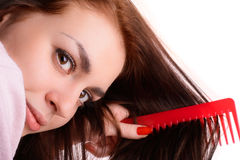 Girl combing her hair red comb Royalty Free Stock Photo