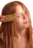 Girl combing long hair. Portrait of cute young girl combing long wet hair, isolated on white background Stock Image