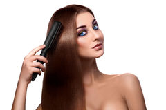 Girl combing perfect long hair and looking at camera with blue e Stock Photos