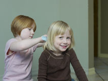 Girl Combing Sister's Blond Hair Stock Photography
