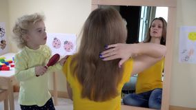Girl combing woman hair in front of mirror. Static closeup shot. 4K UHD stock video footage