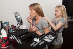 Girl combs mother's hair Stock Photos