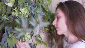 The girl come to the flowers, decorates them with a branch of eucalyptus, then leaves the frame