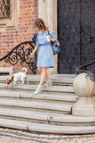 Girl comes down the stairs with a dog and a cup stock photo