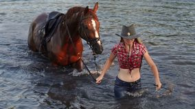 Girl comes out of a lake in clothes with her horse