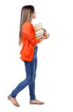 Girl comes with  stack of books. Stock Images