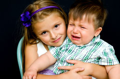 Girl comforting crying baby. Young girl comforting crying baby brother, black studio background Royalty Free Stock Image