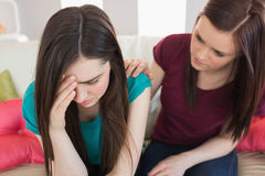 Girl comforting her crying friend on the couch Stock Image