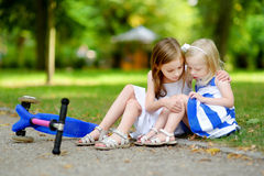 A girl comforting her sister after she fell while riding her scooter Stock Photo