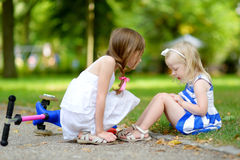 A girl comforting her sister after she fell while riding her scooter. Little girl comforting her sister after she fell while riding her scooter at summer park Royalty Free Stock Photo