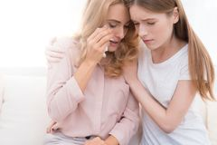 The girl comforts an adult woman who cries. Stock Photography