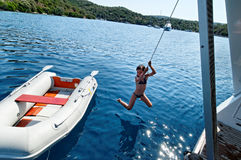 Girl coming ashore from a dingy. Girl in bikini coming ashore from rubber  dingy swinging on the end of a rope Stock Image