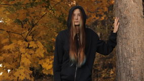 A girl coming out of the depths of the wood stops by a tree against the autumnal leaves and sunset. She holds a tree. With her hand takes the hood off and looks stock video