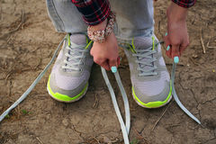 girl commits an outdoor walk and stopped to tie his shoelaces on sneakers. stock photo