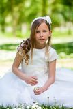 Girl in communion dress holding flowers. Stock Photo
