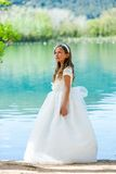 Girl in communion dress at lake. Stock Photography