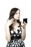Girl with compact mirror Stock Image