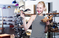 Girl comparing shoes in store Royalty Free Stock Image